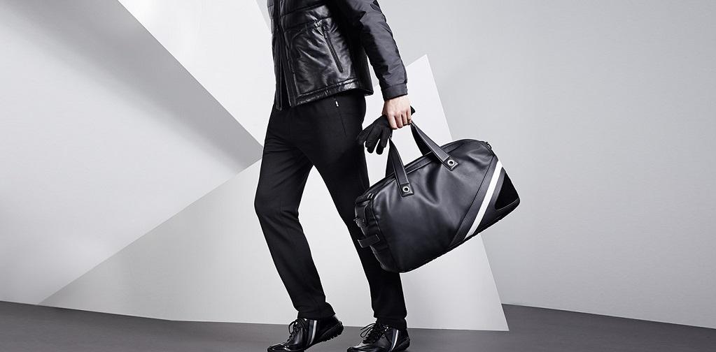 homme habillé en noir avec un sac à la main