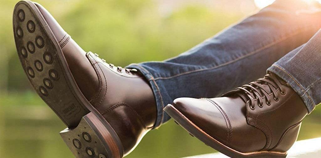 homme portant une paire de bottes montantes marron