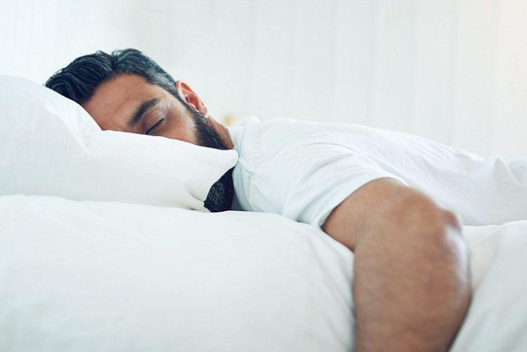 homme dormant sur un lit